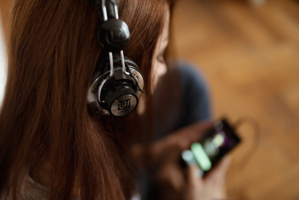 a girl listening to her ipod with large black headphones.