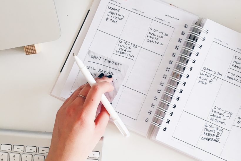 a hand holding a pencil over a white planner on a white desk.