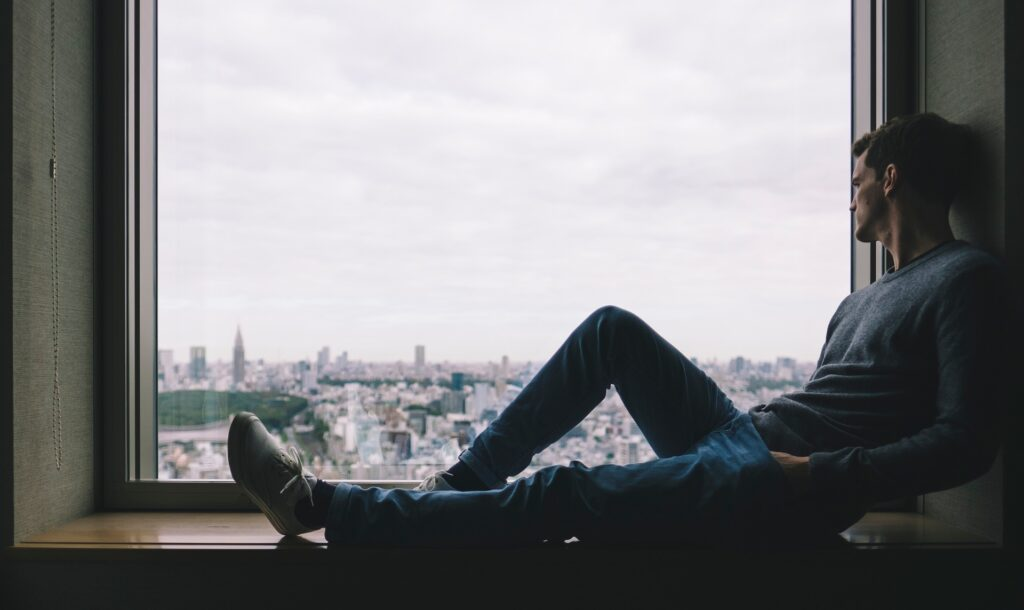 man in a grey sweater and blue jeans sitting on a window sill overlooking the city