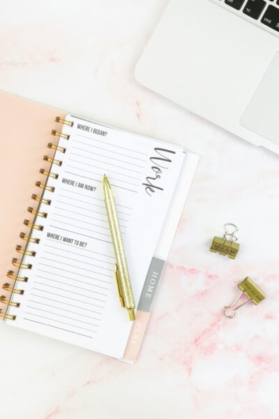 pink planner with golden pen on top of a desk