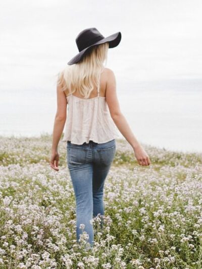 girl in a white shirt walking in a field of flowers