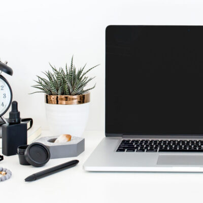 Black computer and black clock on a white desk