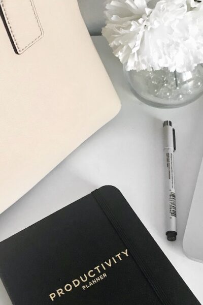 Laptop and black planner on a white desk