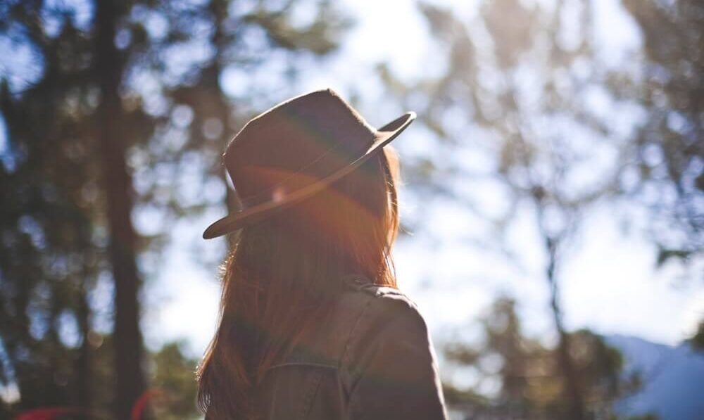 Girl in brown hat and brown jacket standing in sunlight