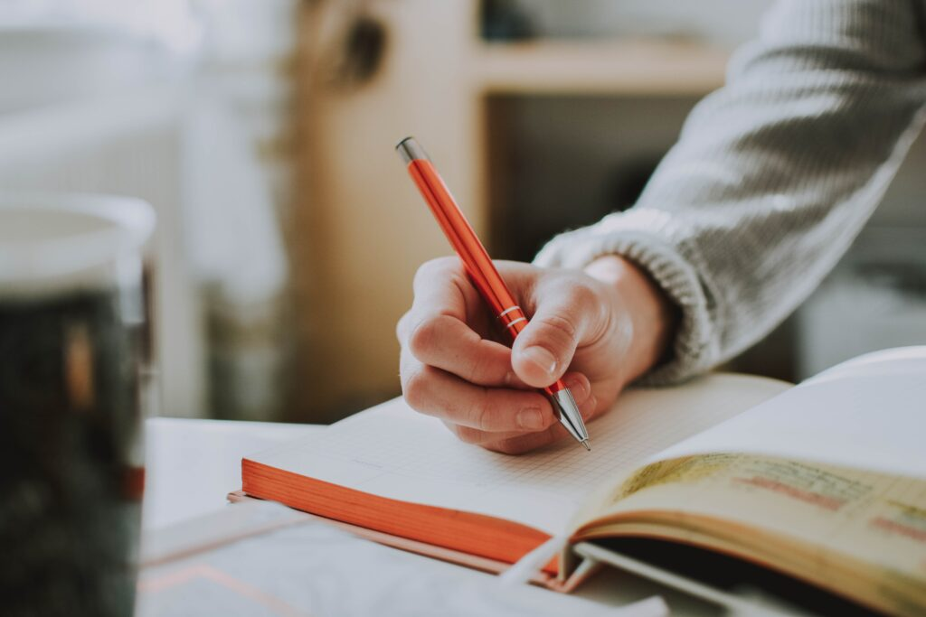 Girl writing in notebook with an orange pen