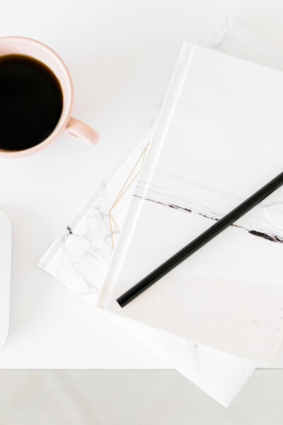 White journal and black coffee on a white desk